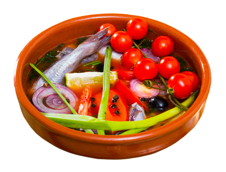 Fisher soup from whiting with tomatoes, red onion, bell pepper served with lemon, scallions, black olives. Isolated over white background