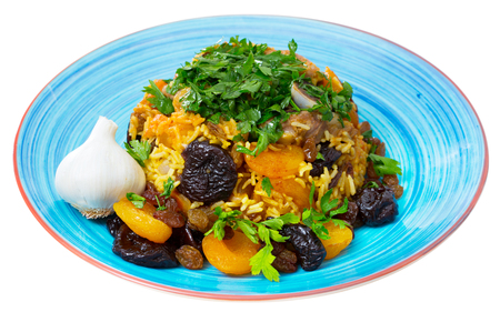 Oriental cuisine - pilaf with lamb, dried plums and apricots, saffron and sweet garlic. Isolated over white background Stock Photo