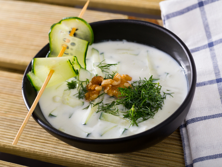 Bulgarian cuisine. Traditional chilled soup Tarator on yogurt with fresh cucumber, dill and walnuts in black plate