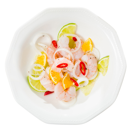Delicious shrimp ceviche with lime, tangerine, onion and hot pepper served on white plate. Isolated over white background 免版税图像