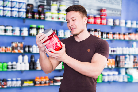 smiling sporty guy looking for necessary food supplements in sport nutrition store Stok Fotoğraf - 115348131