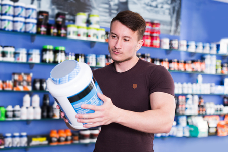 smiling sporty young guy looking for necessary food supplements in sport nutrition store