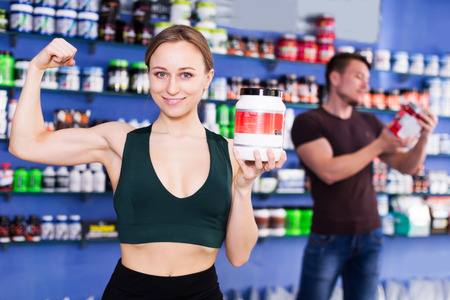 positive athletic girl with jar of sport food supplements showing biceps in shop interior