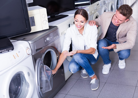 Young happy couple choosing washing machine in hypermarket and smiling