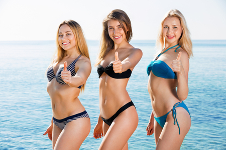 Portrait of three beautiful positive young women in swimsuits on  beach Standard-Bild