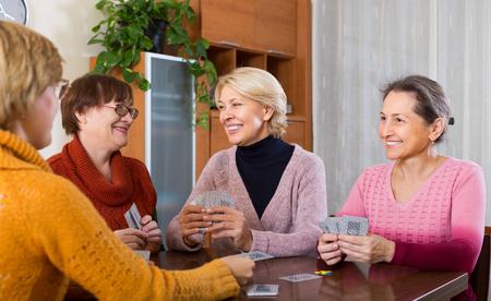 Positive smiling senior mature women playing cards at home Banco de Imagens