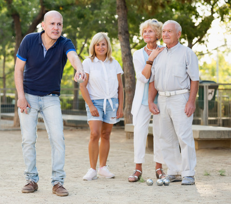 Positive mature people playing petanque in outdoor Stock Photo