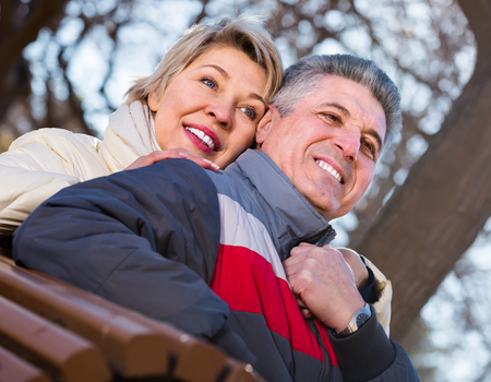 Smiling middle-aged married couple holding hands each other on sunny day in park
