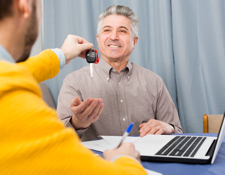 Man and young manager sign contract car rent and hand over keys