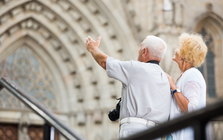 Rear view of senior man pointing to his wife at an old cathedral in joint vacation