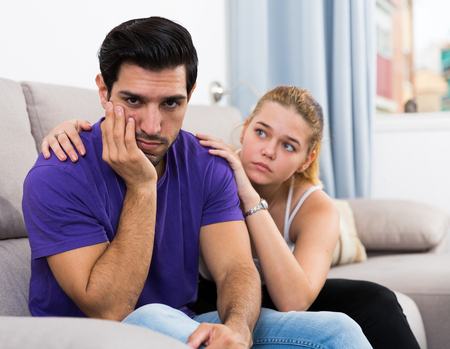 Upset handsome man sitting on sofa at home while girlfriend soothing him