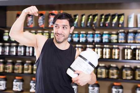 Positive muscular man showing his biceps and holding pot of  sport nutrition