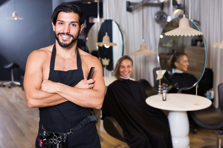 Portrait of sexy adult man hairdresser standing in hairdressing studio
