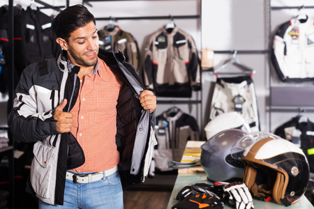 Adult man is trying up jacket-equipment for moto in sport store