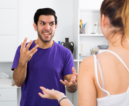 Angry bearded man emotionally gesturing in quarrel with girl