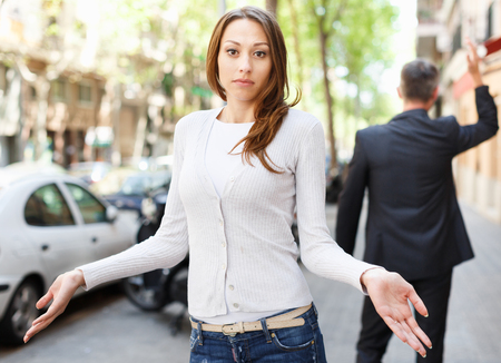 Disappointed young brunette in quarrel with her boyfriend background