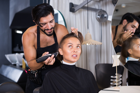 Sexy adult male professional hairdresser cut woman's hair in hairdressing salon Standard-Bild