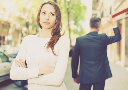 Offended girl on departing boyfriend background after quarrel outdoors