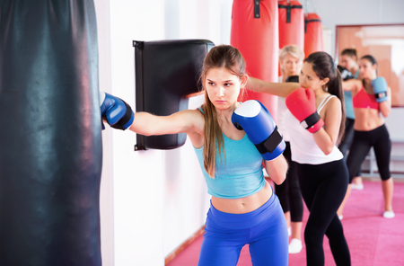 Sporty diligent efficient serious glad girl is boxing near punching bag in gym. Stock Photo