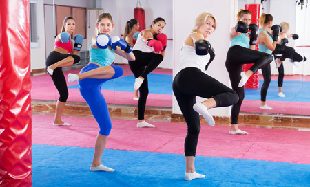serious women are boxing and doing kick with coach in sporty gym. Stock Photo