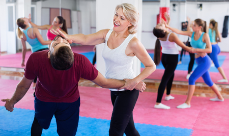 Sporty glad mature woman with her instructor are training self-defence moves in gym. Stock Photo