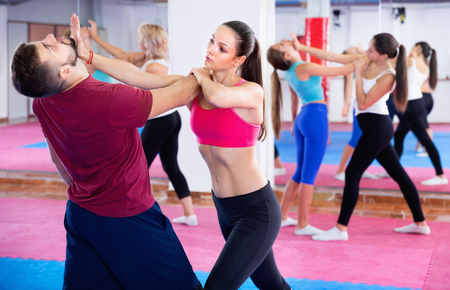 Sporty glad  positive girl with her instructor are training self-defence moves in gym.