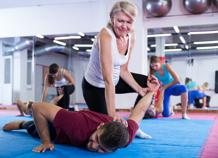 Nice women are doing self-defence-karate moves with trainer in sporty gym