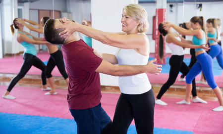Mature woman is training self-defence moves in pair with trainer in sporty gym. Stock Photo