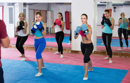 Group of active female are boxing training in sporty gym