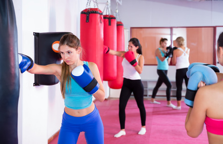 Portrait of young vigorous female who is training box exercises near punching bag in sporty gym Stock Photo