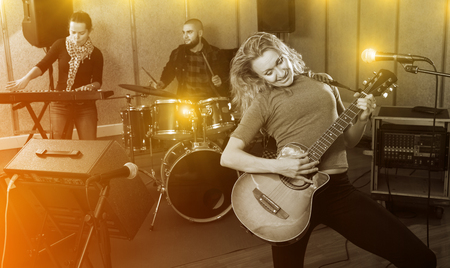 Portrait of happy excited young blonde girl rock singer with guitar during rehearsal with male drummer and female keyboardist in studio