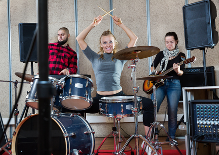 Rehearsal of a music group. Rock band with emotional female drummer playing at recording studio