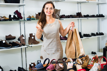 Happy glad young brunette posing with bags in footwear shop Stock Photo