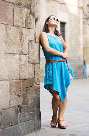Young pretty woman posing during walk on old town streets
