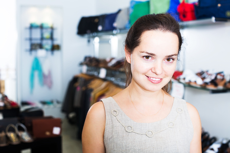 Portrait of young brunette doing shopping in shoes center