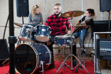 Rehearsal of a music group. Rock band with emotional male drummer playing at recording studio