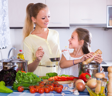 Happy young woman teaching her little daughter to cook vegetarian dish at home kitchen Stock Photo