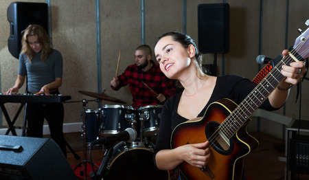Group of young musicians with passionate emotional female vocalist and guitarist practicing in rehearsal room Stock Photo