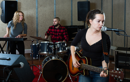 positive excited girl rock singer with guitar during rehearsal with male drummer and female keyboardist in studio