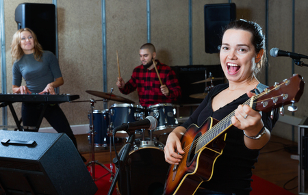 Attractive cheerful  female soloist playing guitar and singing with her music band in sound studio Stock fotó
