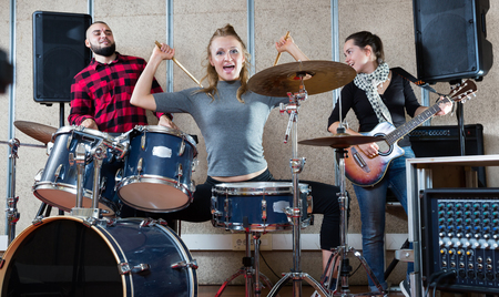 Rehearsal of music group. Rock band with emotional female drummer playing at the recording studio Stock Photo