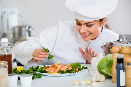 Portrait of positive chef with cooked shrimps in kitchen
