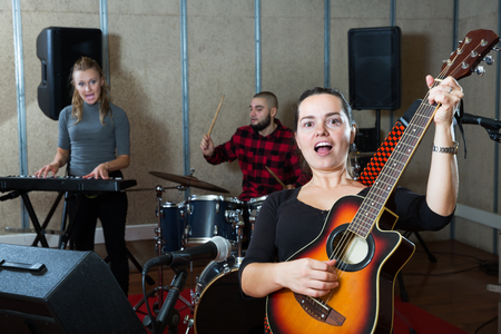 Music garage band with passionate emotional female vocalist and guitarist practicing in sound studio