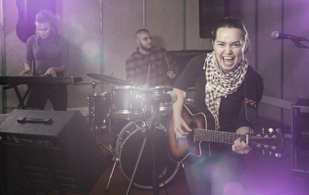 Portrait of active excited cheeful girl rock singer with guitar during rehearsal with male drummer and female keyboardist in studio