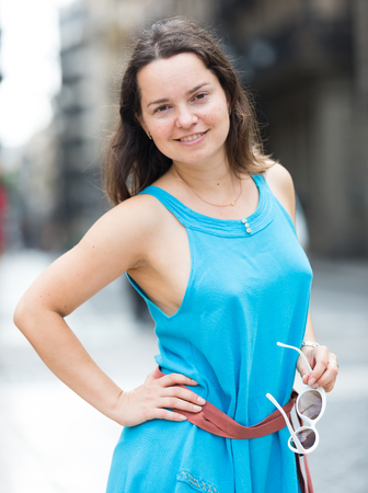 Attractive young girl in summer dress enjoying warm day strolling at city streets Stock Photo