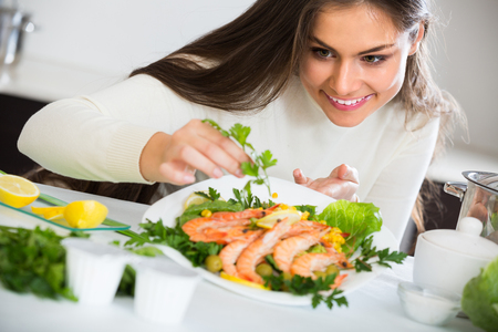 Brunette girl in white pullover decorating plate with fried prawns at home kitchen