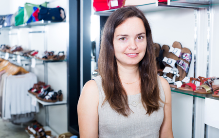 smiling  female seller with dark hair working in shoes store Stock Photo