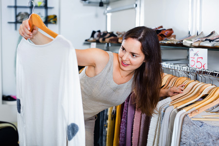 Young woman choosing new long sleeve blouse in apparel shop