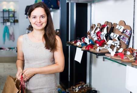 Portrait of smiling young female customer doing shopping in shoes center Stock Photo