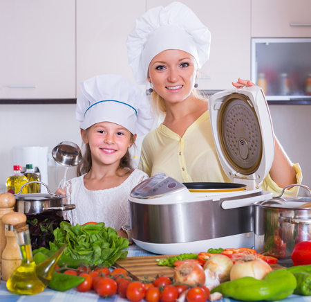 Smiling mother and little daughter with crockpot in home kitchen